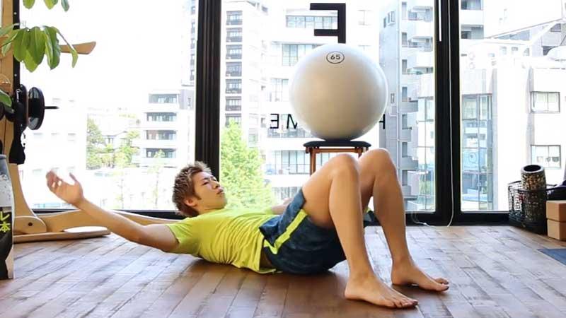スパイン・サイドベント・ ヒール・タッチで腹斜筋を鍛える男性