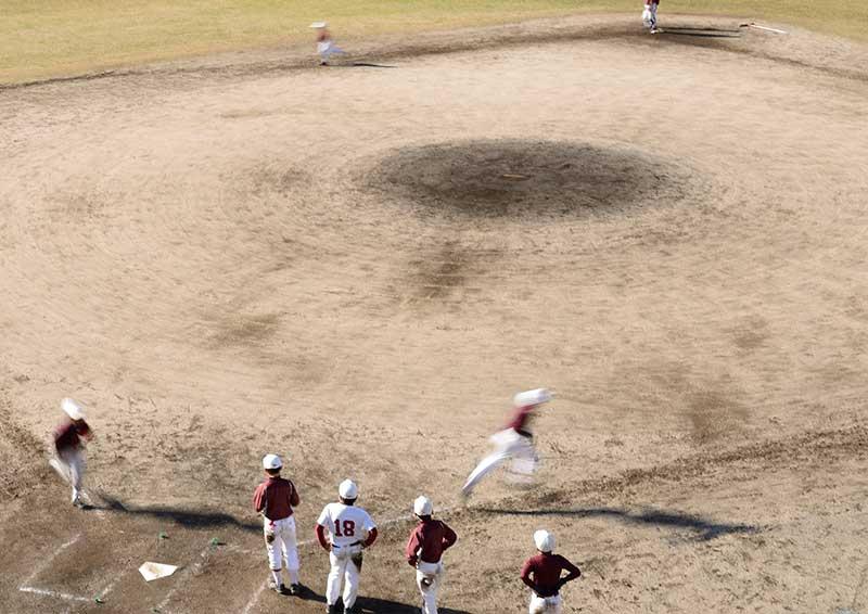 一塁方向へベースランをする野球チーム