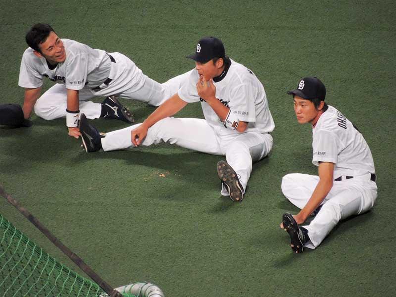 リラックスしながらストレッチを行う野球選手