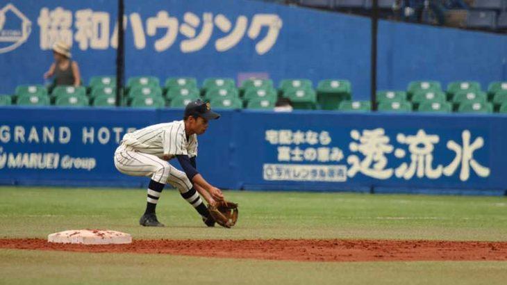守備の捕球態勢をとる大学野球選手