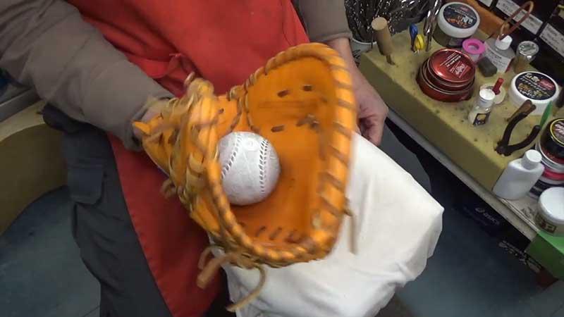 ファーストミットにボールを当てる野球ショップの店長