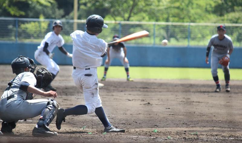 センター返しを打つ高校野球の選手